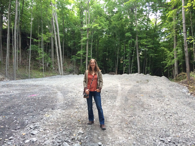 DMO stands in front of flattened gravel in the forest