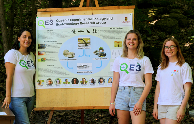students stand beside a poster about the QE3 Research Group